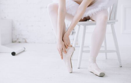 maybe: Young ballerina in white tutu sitting on the stool and holding her right foot with both hands. Maybe she hurt it while she was stretching or dancing Stock Photo