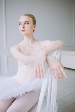 Young delighted and serious ballerina at the same time sitting on the chair and relaxing while looking at the window with a glad face expression. Close up Stock Photo