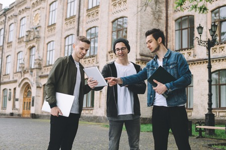 they are watching: Successful students standing near their university and watching funny video on a tablet during the break or they are reading an important article