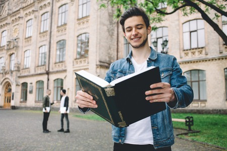 Smiling student in jeans jacket reading a huge book in front f the camera and holding it with both hands standing near the college. Close up photo