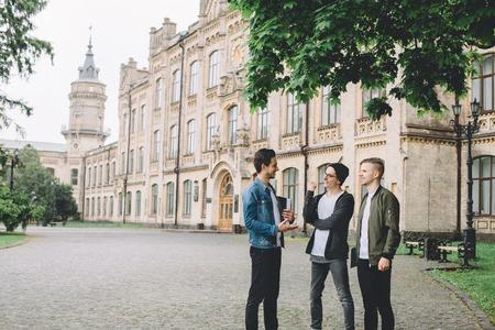 69d6a4f1 Banque d'images - Un étudiant en veste en jeans qui raconte à ses deux  autres amis une histoire drôle de la leçon. Ils rient et se reposent  pendant la pause