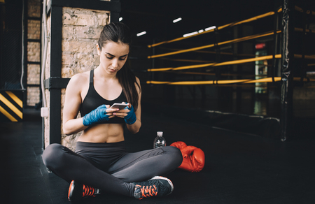 boxing tape: Attractive woman in sportswear sitting near the boxing ring and having some rest. She is scrolling in her mobile phone or chatting with friends Stock Photo