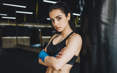 boxing tape: Young sporty girl with crossed arms seriously looking at camera. Focused woman standing with wrapped fists with blue bandage tape and looking at the camera