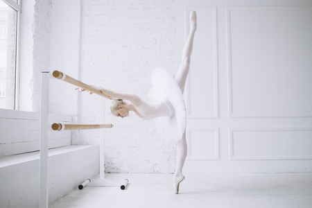 Young gorgeous and slim ballerina doing some exercising in the white ballet room. She is making split holding barre with both hands and with her head down. Close up