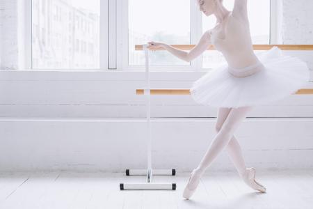 Jonge en elegante ballerina standind in croise derrièrepositie op pointe bij staaf dichtbij groot venster in wit klaslokaal. Ze concentreert zich op het maken van deze positie. Detailopname Stockfoto