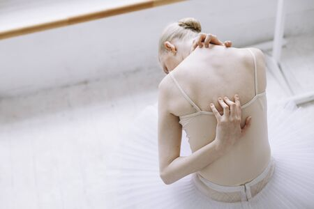 One more close up of a young fragile ballerina sitting on the floor and looking down to it. She has put her arms on her back and neck. Girl is tired. Close up