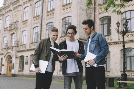 Young guys are standing outside of the universitys building and reading a big interesting book together. Also two of them are holding laptops in they hands. photo