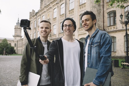 Three handsome guys are standing outside near university where they study. Young men are taking selfies and posing at camera. Close up photo