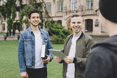 Two friends are standing outside. THeir third friend has just come to meet them so thats why these two guys are smiling. THey are happy to see their friend. Close up photo