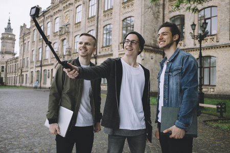 Three students are standing outside of universitys building and taking selfie using a selfie stick during the short break between lessons. photo