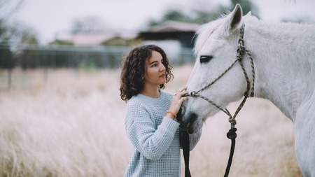 tenderly: Attractive and beautiful woman with black culy hair in a light blue coat tenderly stroking a gorgeous white horse. They are walking outside. Close up Stock Photo