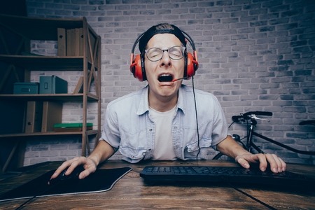 Young man in red headphones and white shirt playing game at home and streaming playthrough or walkthrough video. Poor guy is crying because of fail. His ace expression is amazing and gorgeous.
