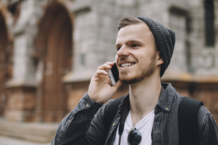 he: The portrait of a young guy talking on the phone. He is enjoying the conversation and smiling. Aparently this man is waiting for somebody. Close up. Cut view. Stock Photo