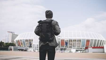The picture of traveller that is standing on the big square and looking to the big white stadium. He has finally finished the trip and its time to go home. But he knows he will come back to this city again. Stock Photo