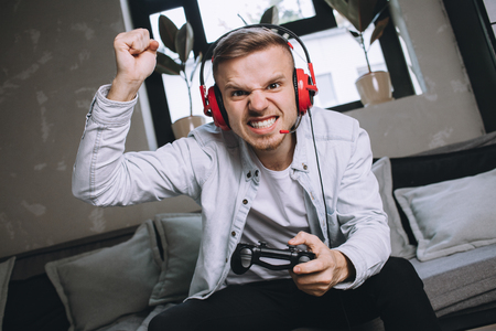 Passionate and attractive gamer has won a competition. The game was really hard so young man cant keep his emotions inside of him. He wants to say Yes, I did that and he really did. Close up