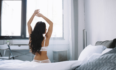 Another picture of an attractive and stunning girl in lingerie sitting at the edge of a bed stretching. Her head is turned to the right. The beaty is ready for a new day.