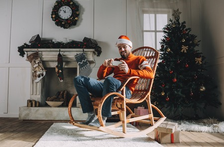 Adult and bearded guy is sitting in the rocking chair in a beautiful white room decorated with Christmas toys, tree and garlands. He is watching a Christmas special series of his favourite program on the phone. Guy is happy and full of joy. Фото со стока