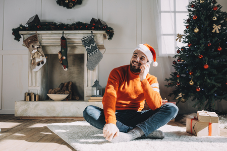 Happy and relaxed guy is sitting on the floor on the fluffy white carpet in a room full of Christams decoration. He is sitting with his legs crossed and talking on the phone with his parents.