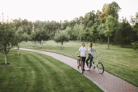 Two young adults have stopped on the road in park to have some rest. They are bikers and enjoy biking from time to time. While they are resting boy and girl is looking to each other with sight full of happiness and love.