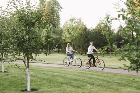 Young man and woman are riding bike in the park this beautiful summer day. He is going in the front while she is going behind him. They are just having some fun together.
