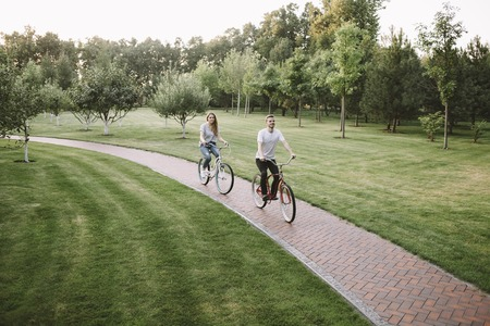 A picture with young boy and girl was made from another angle in green park. Happy couple is riding their bikes on a small road through the meadow. They are coming closer and closer. Фото со стока