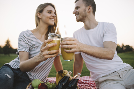 One more close up of beautiful and cheerful couple drinking some orange juice outside in park and looking to each other. They have big plans together for the future where they will be happy. Cut view Фото со стока