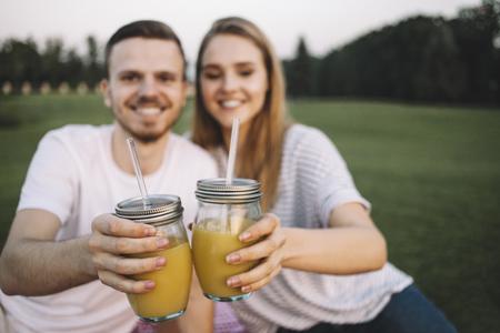 若いカップルは一緒に大きなグリーパークに座って、いくつかのジュースをドリングしています。少女がどこか下を見ている間、少年はカメラをまっすぐに見ている。彼らはお互いの会社を楽しんでいる。クローズアップ。ビューのカット