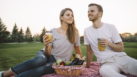 Close up of boy and girl sitting on mat in the green park. They have a basket with food and tow glasses with orange juice. Young couple is just enjoying the company of one another and nothing more. Cut view