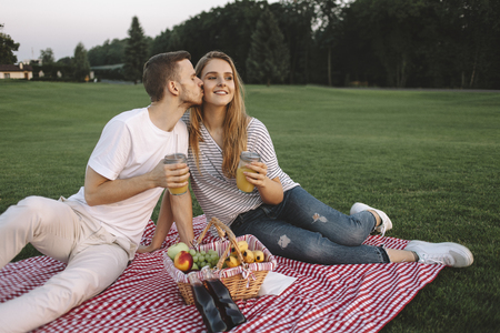 One more close up of stylish and good-looking young man and woman sitting in big green park when the sun goes down. They have a free weekend so they wanted to have some fun and joy. And its a lovely moment when boy is kissing his girlfriend. Cut view Фото со стока