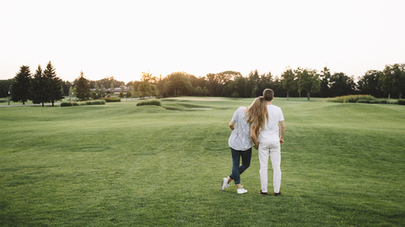 Nice picture of two people - man and woman - standing together and holding each other to the hand and looking to the sunset. They had a nice day-off in park. But now its time to go home.
