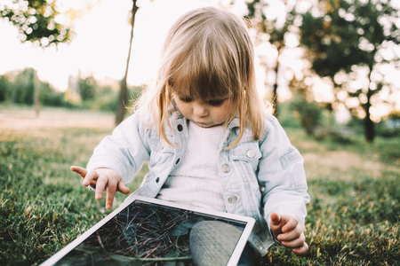This cutie is sitting on the small meadow near trees and holding a huge laptop on her knees. This bulky gadget coveres all of her legs. Despise that the girl is looking to tablets screen that shows beautiful picture of grass on it. Close up. Cut view Фото со стока