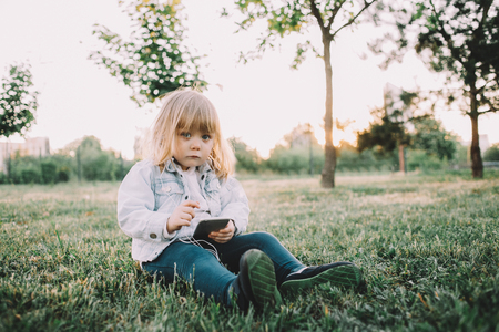 Modern and stylish child is sitting on the grass in park and holding a phone in her hands. Also she has earplugs plugged to her phone. She is listening to the music and looking straight to the camera with serious sight.