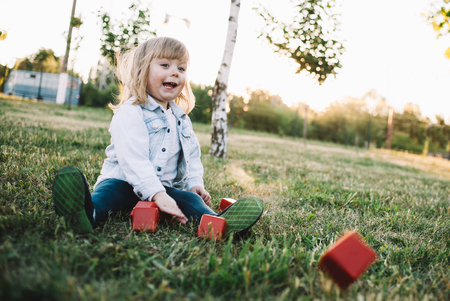 Happy and cheerful kid is throwing cubes forward on the green meadow at the end of this beautiful day. She is happy to do that.