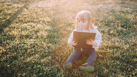 Cute and nice small blonde girl is sitting on the grass in the middle of park and holding a tablet in her hands. She is looking somewhere aside with curiosity. The last sunlight is lightning both the grass and the body of a girl.