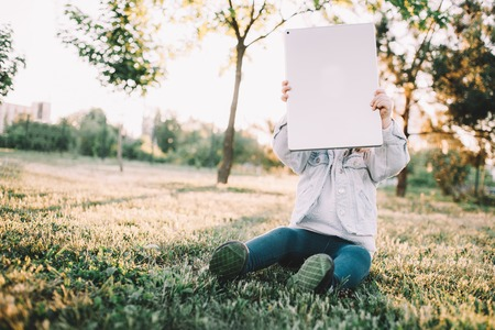 Another picture of a small kid sitting on grass and holding a tablet in front of her face. She is thinking she can hide from imagine monster in that way.
