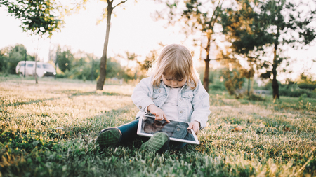 A cute picture of small little girl sitting on grass and playing with big tablet. She wants to watch some cartoons on it so thats why she is pointing on the screen.