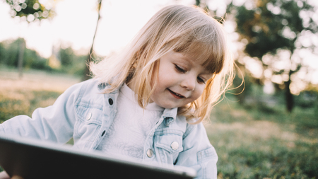 Cool and small blonde is sitting on the grass alone in the park and holding a tablet in her hands. Smart kid knows how to handle with this big bulky thing and find cartons on it. Thats why she is looking on the tablets screen. Close up. Cut view Banque d'images