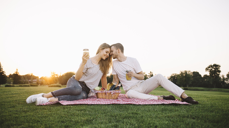 What a nice picture Beautiful couple is sitting on mat in the middle of park when the sun goes down and touching one another. They are enjoying the feelling of being so close to whom who you love. Its magnificent