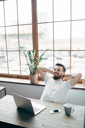 Vertical picture of bearded man sitting at the table and relaxing. He is near tbig window. Guy is relazing and listening to the music on the phone