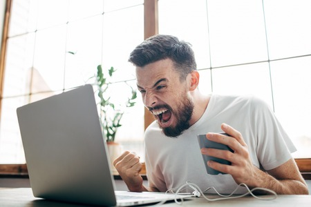 Angry man is sitting in the room near big window and looking to the laptops screen. He is angry. Guy is screaming to the screen. Also he is holding a cup of tea in the left hand