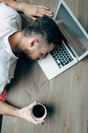 Vertical picture of guy sitting at the table. He is holding a cup of coffee. He has put his head over the laptop. Young man is sleeping. He is tired. Cut view Фото со стока