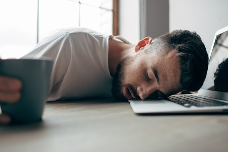 Tired guy is sleeping. He has put his head on the keyboard of the laptop. Also he is holding a cup of tea. This man is exausted. Cut view Фото со стока