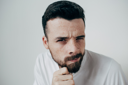 Portrait of doubtful guy looking straight to the camera. He is holding his fingers close to the face. Young man is wondering about something. Isolated on white background Фото со стока
