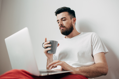 Nice picture of working man sitting near the wall. Guy is looking to the screen and drinking a cup of coffee at the same time. This man is concentrated very much