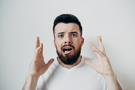 Portrait of irritaited man that is looking straight to camera and keeping his hands up. He is very nervous. Isolated on white background Фото со стока