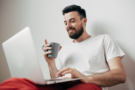 A picture of smiling and cheerful guy sitting on the floor near white wall and working from home. He has laptop on his legs. Also man is holding a cup of tea and enjoying the moment