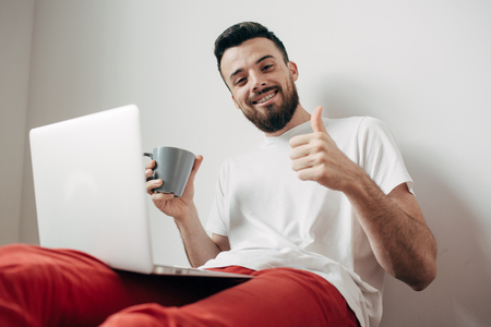 Attractive guy is sitting on the floor and showing his big thumb up on one hand. H is holding a cup of tea with the other one. He looks happy and satisfied