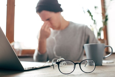 A picture of tired guy sitting at the table and rubbing his eyes. He wants to have some rest after very productive and hard work in front of the laptop. There are glasses in the front