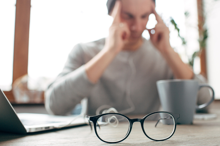 This man is sitting at the table and keeping his eyes close. Also he is holding his fingers close to the head. He has a headache and he is tired. There are glasses in the front of the picture Фото со стока