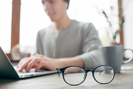 Cut view of a guy sitting at the table and wokring. He is wokring using the laptop. Besides the laptop there is a cup of tea. There are glasses in the front of the picture